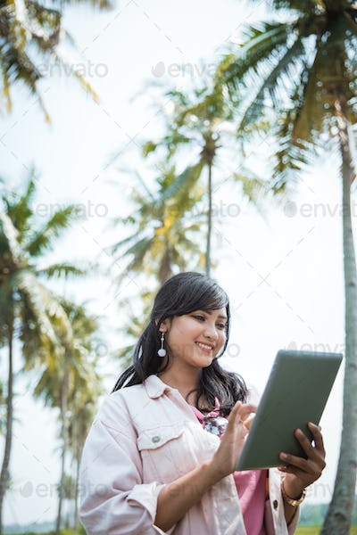 asian woman using tablet pc under coconut trees