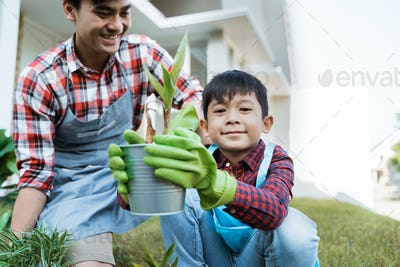 dad and son planting a plant gardening at their house together