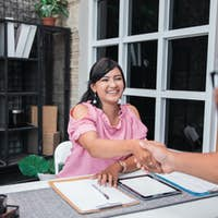 attractive asian woman shake her hand with partner