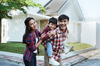 asian family standing in front of their new house together
