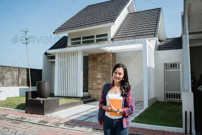 female asian student in front of her house