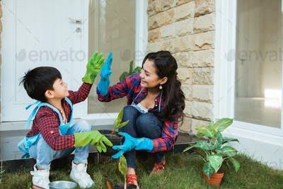 mother and son highfive while gardening together at home