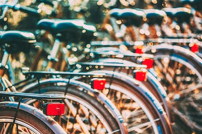 Row of city parked bicycles bikes for rent on sidewalk in Europe