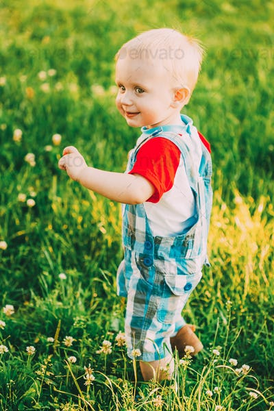 Little Boy Child Running On Green Meadow