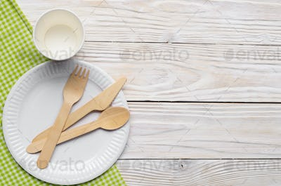 Wooden single use kitchenware in paper plate on table. Top view,