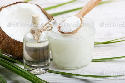 Coconut shell liquid and hard oil in glass jar on white wooden t