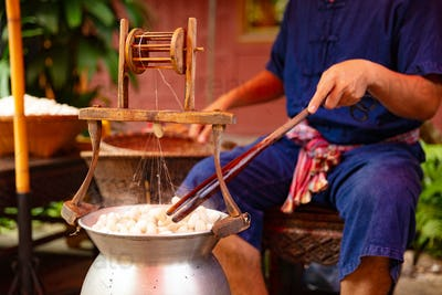Man Unwinding Silk From Cocoons In Large Hot Pot