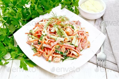 Salad of sausage and spicy carrots with mayonnaise on light tabl