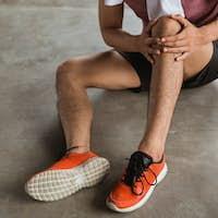 male hand holding knee injury