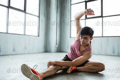 asian young man doing abdominal stretching before workout