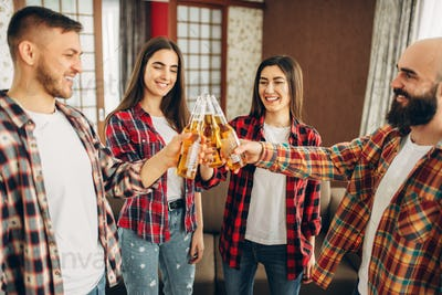 Friends clink bottles with beer at the home party
