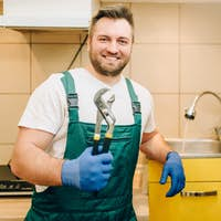 Plumber in uniform holds wrench, handyman