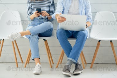 couple is using a laptop and smartphone