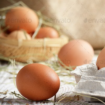 Raw organic brown chicken eggs in square wicker basket on white