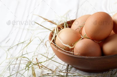 Raw organic brown chicken eggs in clay bowl on white kitchen woo