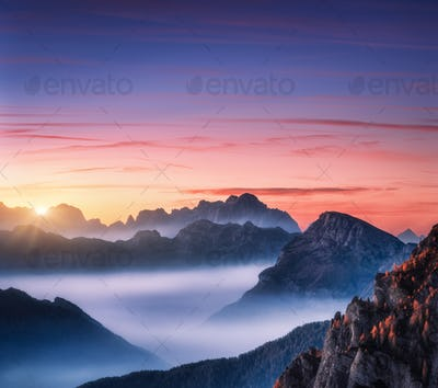 Mountains in fog at beautiful sunset in autumn