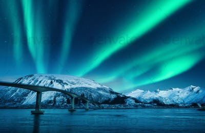 Bridge and aurora borealis over snowy mountains at night