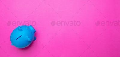 Piggy bank blue color against bright pink background