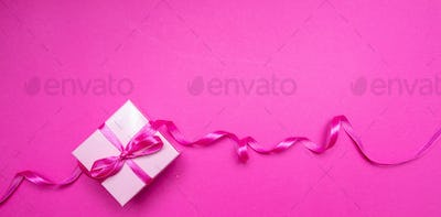 Gift box with ribbon on pink background. Birthday present concept.