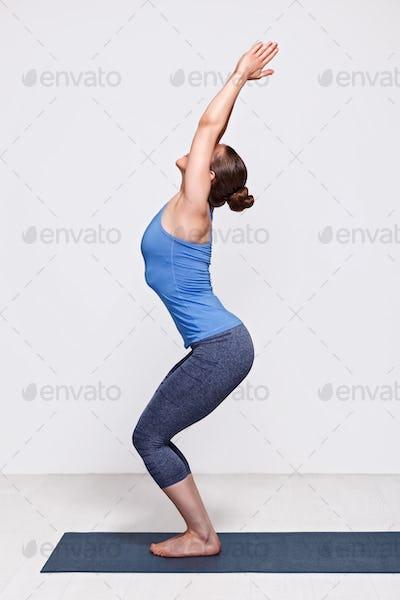 Woman doing ashtanga vinyasa yoga asana Utkatasana