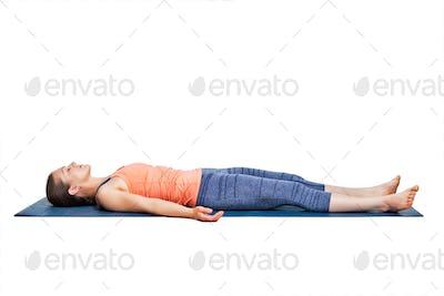 Sporty woman relaxes in yoga asana Savasana