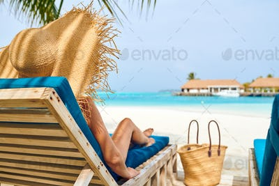 Woman at beach on wooden sun bed loungers