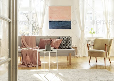 Fashionable retro chair next to elegant grey couch with pillows and blanket