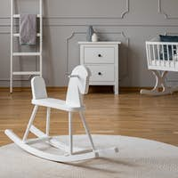 White rocking horse on rug in baby's bedroom interior with poster above cabinet. Real photo