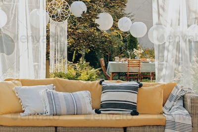 Patterned pillows on the garden settee, real photo