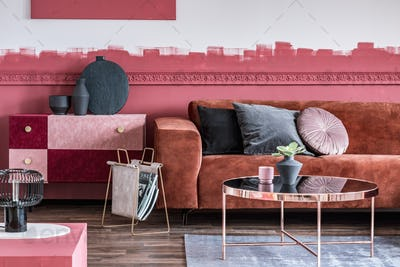 Fashionable living room with ombre wall and brown velvet corner sofa with pillows