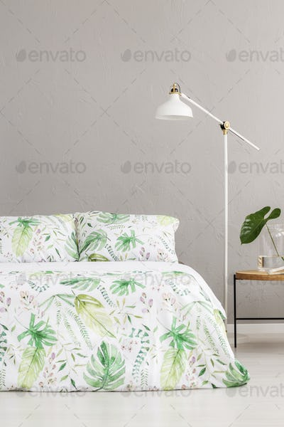 White lamp between wooden nightstand and king size bed