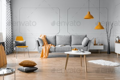 Fashionable living room interior design with grey couch, wooden coffee table and orange accents