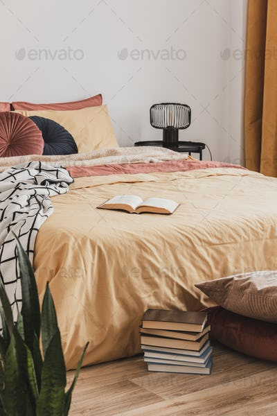 Pile of books in foot of king size bed with yellow duvet and ginger pillows