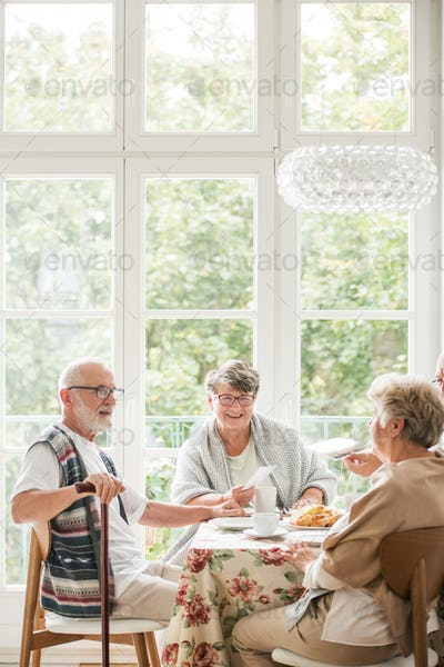 Group of senior friends enjoying coffee during meeting at home