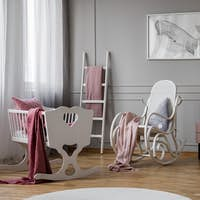 White cradle next to rocking chair in grey baby's bedroom interior with whale poster. Real photo