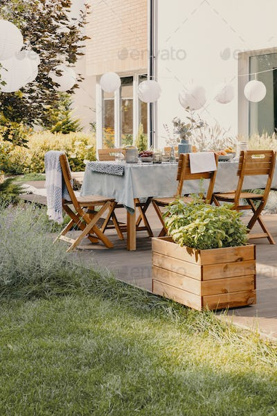 Real photo of a garden with a table, chairs, lamps and wooden box with plants