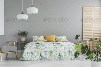 Double bed with botanical accents on sheets and peach colored pillows