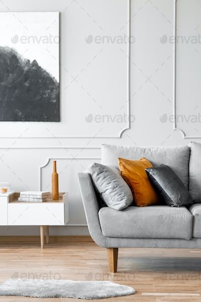 Poster above cabinet next to couch with pillows in grey living room interior with fur. Real photo