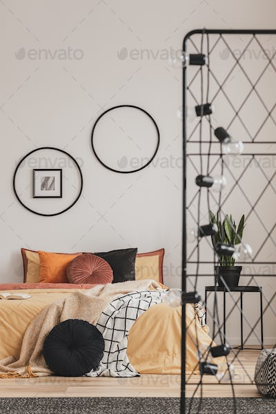 Light bulbs on metal screen in fashionable bedroom interior