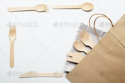 Wooden single use kitchenware in paper shopping bag on white. To