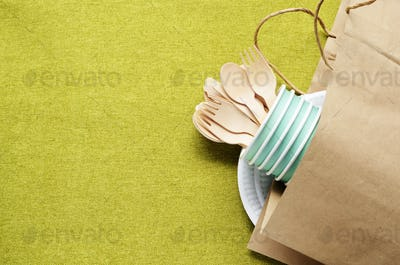 Wooden single use kitchenware in paper bag on table. Top view, s