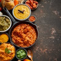 Assortment of various kinds of Indian cousine on dark rusty table