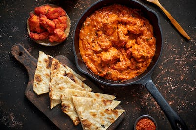 Traditional Indian chicken tikka masala spicy curry meat food in cast iron pan