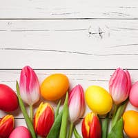 Fresh colorful tulips and easter eggs on wooden background