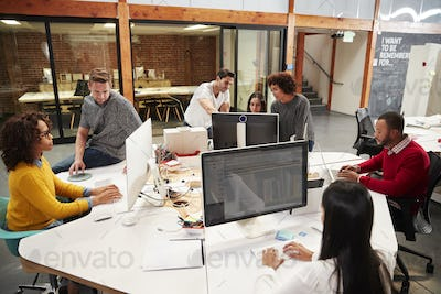 Casually Dressed Business Team Working At Desks In Modern Open Plan Office