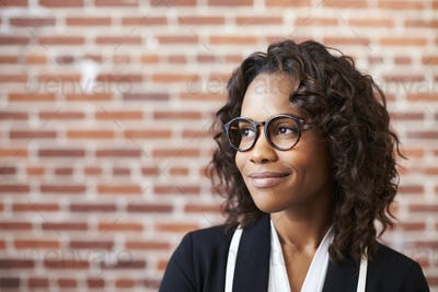 Smiling Businesswoman Wearing Glasses Standing Against Brick Wall In Modern Office