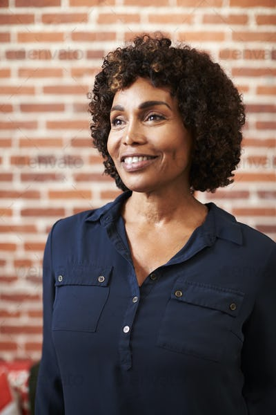 Smiling Mature Businesswoman Standing Against Brick Wall In Modern Office