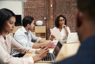 Businesswoman Leading Office Meeting Of Colleagues Sitting Around Table