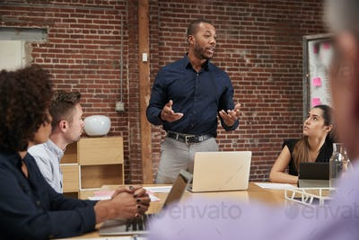 Businessman Standing And Leading Office Meeting Around Table