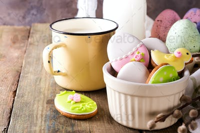 Eggs shaped Easter cookies, hand-made with cup of milk. Decorated with fondant icing on old wooden